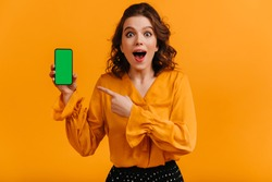 Excited woman pointing with finger at digital device. Studio shot of shocked girl holding smartphone with blank screen.