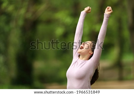 Excited woman raising arms and screaming celebrating in a green forest Foto stock ©