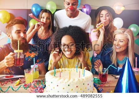 Excited woman ready to blow out candles on white frosting cake on table at birthday party with happy friends Foto stock ©