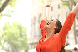Excited woman wearing orange blouse raising arms outdoors in the street with buildings in the background