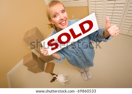 Excited Woman with Thumbs Up and Doggy Holding Sold Real Estate Sign Near Moving Boxes in Empty Room Taken with Extreme Wide Angle Lens.