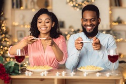 Excited young african american couple sitting in restaurant and taking pictures of food with mobile phones for social media, foodie bloggers celebrating St Valentine's Day together