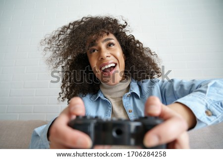 Excited young african american ethnic teen girl gamer holding gamepad joystick controller playing videogame sitting on sofa at home. Happy black woman player enjoying video gaming at home concept.