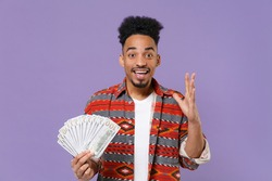 Excited young african american guy in casual colorful shirt isolated on violet background. People lifestyle concept. Mock up copy space. Hold fan of cash money in dollar banknotes, spreading hands