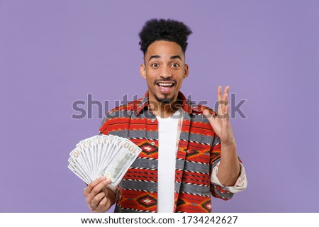 Excited young african american guy in casual colorful shirt isolated on violet background. People lifestyle concept. Mock up copy space. Hold fan of cash money in dollar banknotes, spreading hands Сток-фото ©