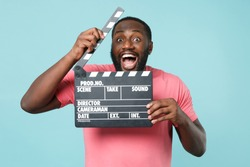 Excited young african american man guy in casual pink t-shirt isolated on blue background studio portrait. People lifestyle concept. Mock up copy space. Hold classic black film making clapperboard