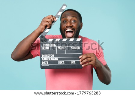 Photo of  Excited young african american man guy in casual pink t-shirt isolated on blue background studio portrait. People lifestyle concept. Mock up copy space. Hold classic black film making clapperboard