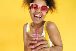 Excited young african teen hipster gen z girl holding drink look at camera wear pink glasses enjoy cool cocktail laughing isolated on yellow party summer studio background. Head shot closeup portrait.