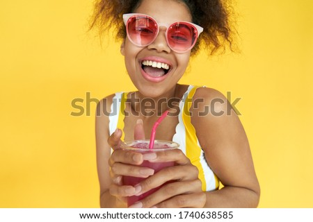 Excited young african teen hipster gen z girl holding drink look at camera wear pink glasses enjoy cool cocktail laughing isolated on yellow party summer studio background. Head shot closeup portrait. Photo stock ©