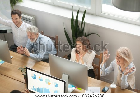 Excited young and old colleagues applauding celebrating corporate success, happy motivated business team clapping hands congratulating coworkers with good news result achievement, overhead top view