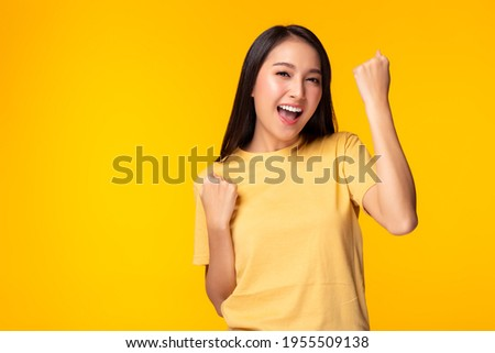 Excited young asian female with raised hands celebrating success Portrait cheerful positive asian woman with raised hands and fists open mouth Girl get happy, enjoy life yellow background, copy space
