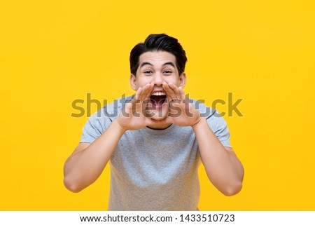 Excited young Asian man shouting with hands cupped around mouth isolated on yellow background