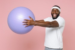 Excited young bearded african american fitness sports man in white headband t-shirt posing hold fitball looking camera spending time in gym isolated on pastel pink color background studio portrait