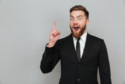 Excited young bearded businessman having an idea and pointing finger up at copy space isolated over gray background