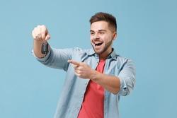 Excited young bearded guy 20s in casual shirt posing isolated on pastel blue wall background studio portrait. People emotions lifestyle concept. Mock up copy space. Pointing index finger on car keys