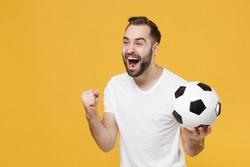 Excited young bearded man football fan in white t-shirt cheer up support favorite team with soccer ball screaming clenching fist isolated on yellow background. People sport family leisure concept.