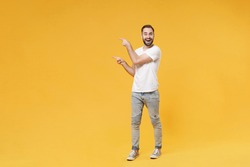 Excited young bearded man guy in white casual t-shirt posing isolated on yellow background studio portrait. People sincere emotions lifestyle concept. Mock up copy space. Pointing index fingers aside