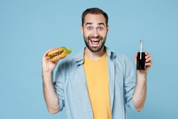 Excited young bearded man guy 20s wearing casual clothes posing holding in hands american classic fast food burger bottle of cola isolated on pastel blue color wall background studio portrait