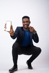 excited young black business man showing his phone screen to the camera and pointing to it