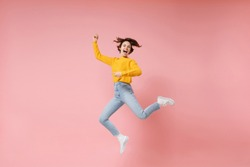 Excited young brunette woman girl in yellow sweater posing isolated on pastel pink background in studio. People lifestyle concept. Mock up copy space. Having fun fooling around, rising hands, jumping