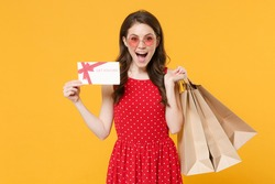 Excited young brunette woman 20s in red summer dress eyeglasses posing isolated on yellow background studio. People lifestyle concept. Hold package bag with purchases after shopping gift certificate
