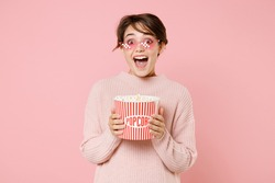 Excited young brunette woman wearing knitted casual sweater 8 bit glasses isolated on pastel pink background. People emotions in cinema, lifestyle concept. Watching movie film, hold bucket of popcorn