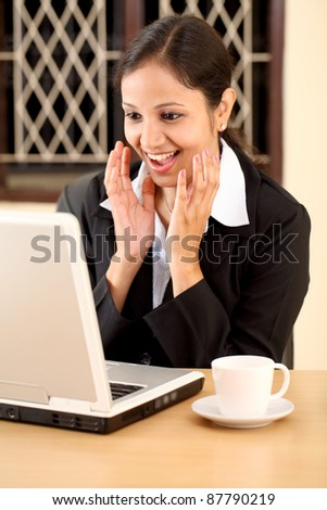 Excited young business woman with laptop