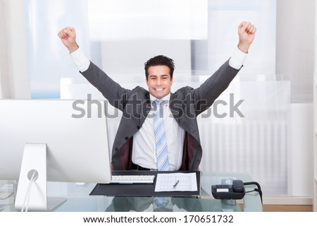 Excited Young Businessman Raising His Hands In Joy