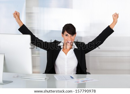 Excited Young Businesswoman With Arm Raised Sitting At Desk