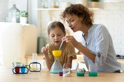 Excited young Caucasian mother and little 9s daughter have fun play with chemistry lab game together. Caring playful mom and small teen girl child engaged in interesting scientific activity at home.