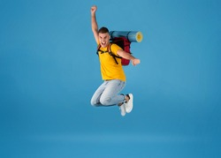 Excited young Caucasian tourist with camping equipment jumping on blue studio background. Full length portrait of funky guy thrilled over his summer holiday camping trip