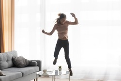 Excited young Caucasian woman have fun jumping dancing celebrate win in living room at home, happy overjoyed millennial girl in glasses feel crazy with unexpected good news or message on cellphone