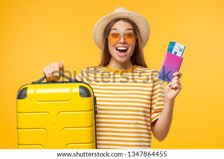 Excited young cheerful female tourist holding large suitcase and passport with flight tickets, isolated on yellow background