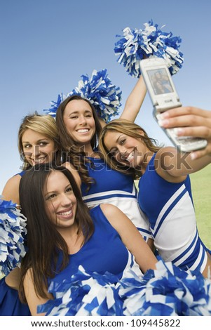Excited young cheerleaders taking self-portrait through cell phone