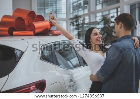 Excited young couple hugging, celebrating buying new automobile together at car dealership. Beautiful cheerful woman holding up car keys, embracing her husband after buying new car #1274356537