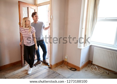 Excited Young Couple Opening Front Door Of New Home #1273188100