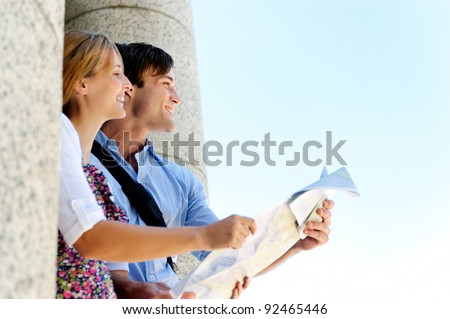 excited young couple traveling, they look at a map while visiting an old tourist attraction monument