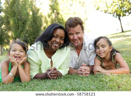 Excited young family lying down on the grass