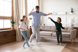 Excited young father enjoying funny family activity with small kids in living room. Energetic little children siblings dancing to favorite pop music with cheerful daddy at free weekend time at home.
