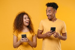 Excited young friends couple african american guy girl in casual clothes isolated on yellow orange background. People lifestyle concept. Mock up copy space. Using mobile phone, looking at each other