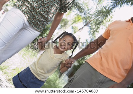 Excited young girl holding hands while walking with parents in park