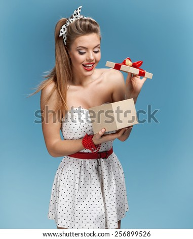 Excited young girl opening present box / set photos of beautiful young retro pinup woman on blue background