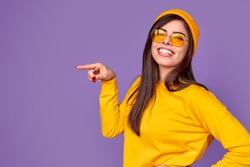 Excited young hipster in bright yellow outfit smiling and looking at camera while pointing at empty space on violet background