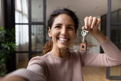 Excited young hispanic lady tenant buyer wish to keep in memory moving to new home take selfie on phone with keys in hand. Happy woman proud of buying flat make video call to friend show key to camera