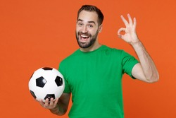 Excited young man football fan in green t-shirt cheer up support favorite team with soccer ball showing OK sign isolated on orange background studio portrait. People sport leisure lifestyle concept