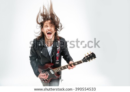 Excited young man in black leather jacket with electric guitar shouting and shaking head over white background #390554533