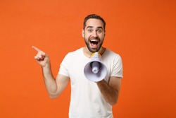 Excited young man in casual white t-shirt posing isolated on orange wall background. People sincere emotions lifestyle concept. Mock up copy space. Screaming in megaphone, pointing index finger aside