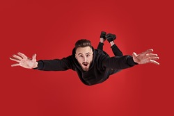 Excited young man is flying through the air in a state of gravity.  Studio portrait on a red background.