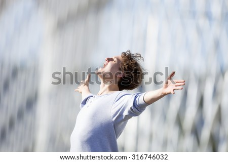 Excited Young Man Stretching out his Arm in Emotion Outdoors