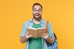 Excited young man student in casual clothes glasses with backpack isolated on yellow background studio portrait. Education in high school university college concept. Mock up copy space. Reading book